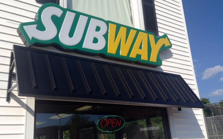 Subway's iconic sign is shown outside a restaurant.