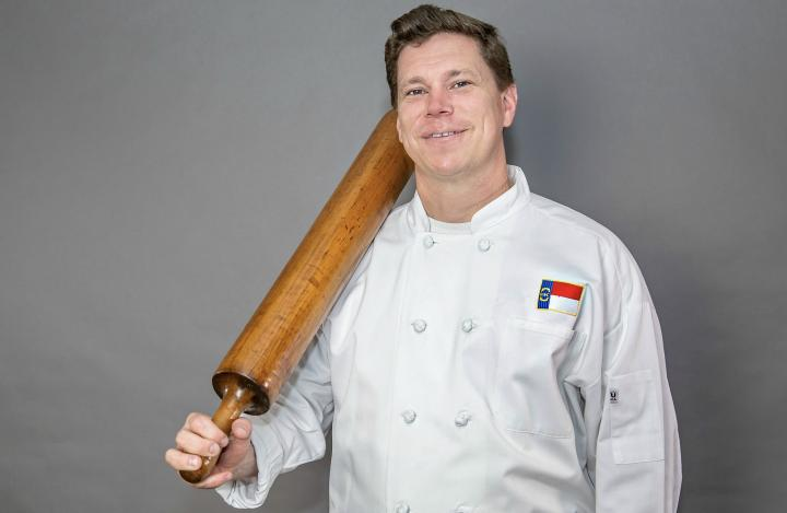 Chef in a white coat holding a rolling pin against a grey background