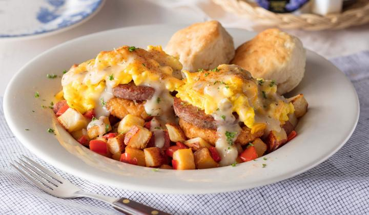 Sausage, Grits Cakes n' Green Tomato Gravy Bowl: Features two deep-fried stone-ground pimento cheese grits cakes and new sweet pepper n' red skin hash topped with sausage patties, two scrambled eggs, and shredded Colby cheese.