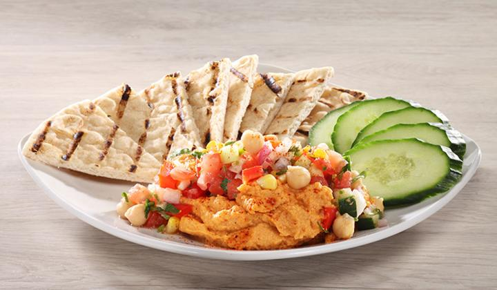 Roasted Pepper Hummus with fire-roasted red bell and jalapeño peppers, tomato corn relish, cucumbers and grilled flat bread