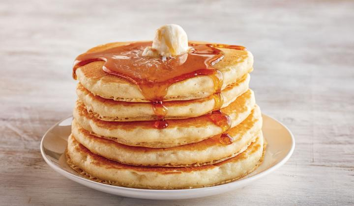 A stack of IHOP pancakes shown with syrup, an American classic that isn't going out of style.