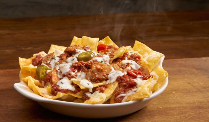 Olive Garden's Pasta Nachos take homemade pasta chips that are lightly fried and layered with Italian cheeses and a hearty meat sauce. Then they're topped with cherry peppers and an Alfredo drizzle.