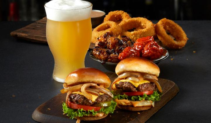 Two burgers, onions rings, and a beer at TGI Fridays.