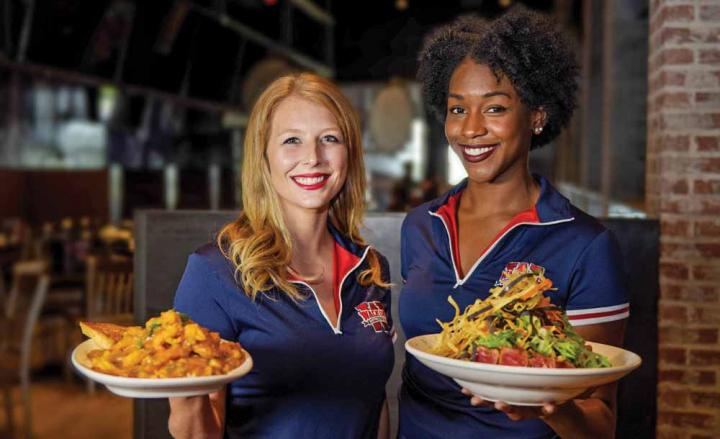 Walk-On's Sports Bistreaux servers hold up plates of food.